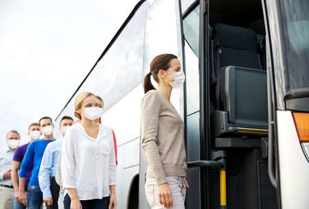 group of passengers in masks boarding travel bus