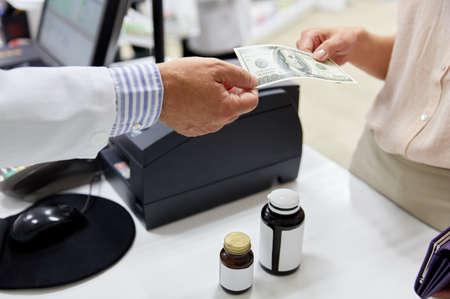 pharmacist taking money from customer at pharmacy Foto de archivo