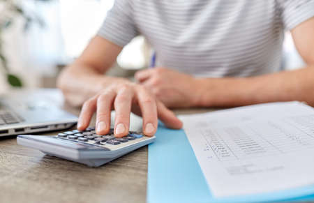 man with files and calculator works at home office