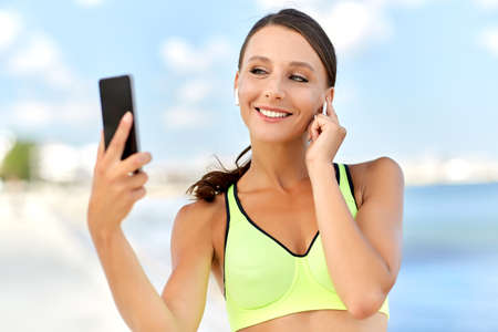 woman with earphones and smartphone doing sports Imagens