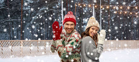 couple in ugly sweaters on christmas ice rink