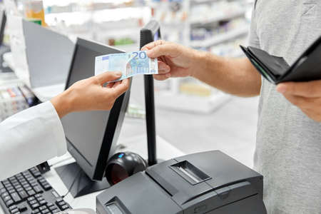 pharmacist taking money from customer at pharmacy