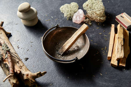 palo santo stick in cup and staff for magic ritual