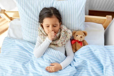 sick coughing girl lying in bed at home