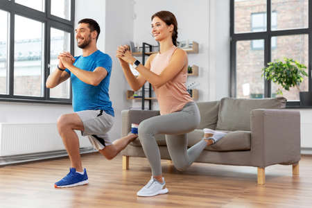 happy couple exercising and doing squats at home Stock Photo