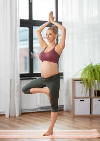 happy pregnant woman doing yoga at home Stockfoto