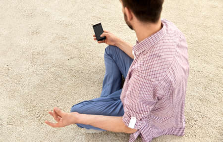 close up of man with smartphone meditating at home