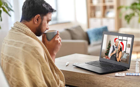 sick man having video call with friends at home Stock Photo