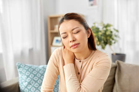 asian woman suffering from ache in neck at home