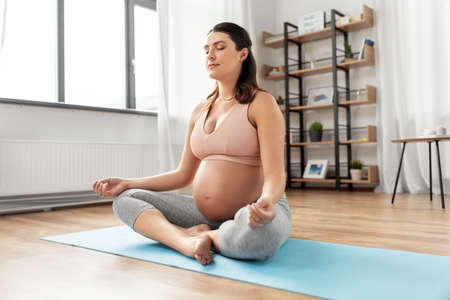 happy pregnant woman meditating at home