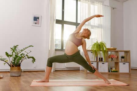 happy pregnant woman doing yoga at home Фото со стока