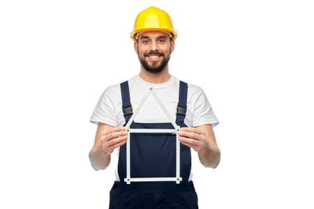 happy male worker or builder with carpenters rule