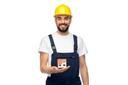 happy male builder holding model of living house Stockfoto