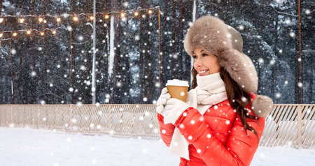 happy woman with coffee cup over winter ice rink