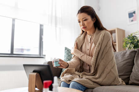 sick woman with medicine has video consultation