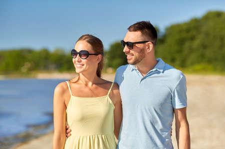 happy couple hugging on summer beach