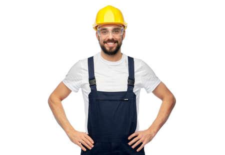 happy male worker or builder in helmet and overall Zdjęcie Seryjne
