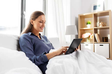 young woman with tablet pc in bed at home bedroom