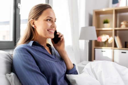 happy woman calling on smartphone in bed at home Zdjęcie Seryjne