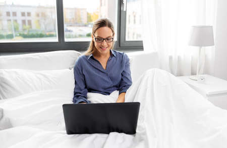 young woman with laptop in bed at home bedroom Zdjęcie Seryjne