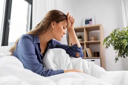 sleepy or stressed woman sitting in bed at home Zdjęcie Seryjne