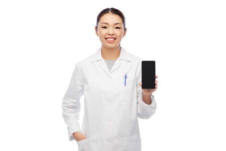 happy asian female doctor or nurse with smartphone Zdjęcie Seryjne