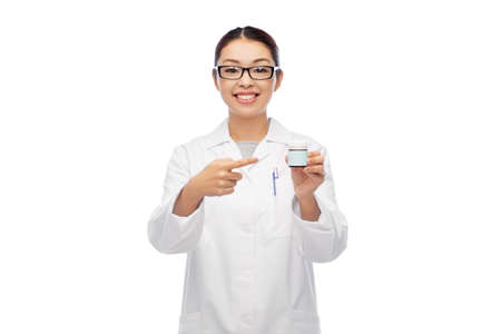 smiling asian female doctor or nurse with medicine