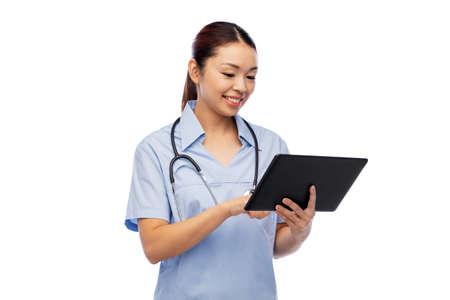 asian female nurse with tablet pc and stethoscope Zdjęcie Seryjne