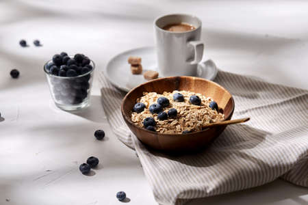 oatmeal with blueberries, spoon and cup of coffee