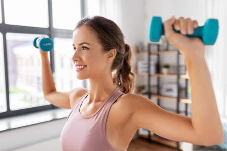 smiling young with dumbbells exercising at home Zdjęcie Seryjne
