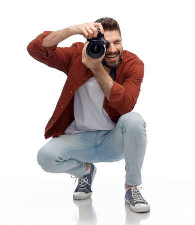 smiling man or photographer with digital camera
