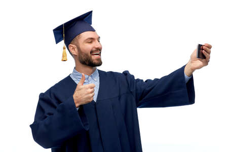 male graduate student with smartphone takes selfie