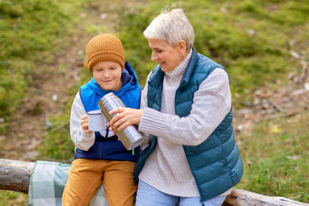 grandmother with grandson drinking tea in forest