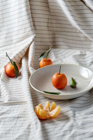still life with mandarins on plate over drapery