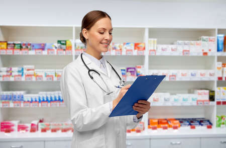 happy smiling female doctor with clipboard