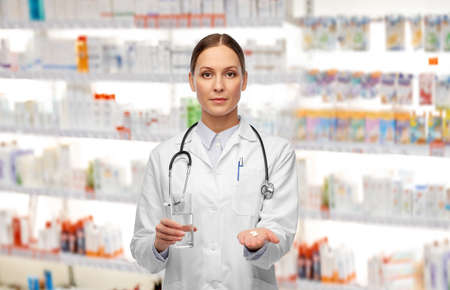 doctor with pills and glass of water at pharmacy Foto de archivo