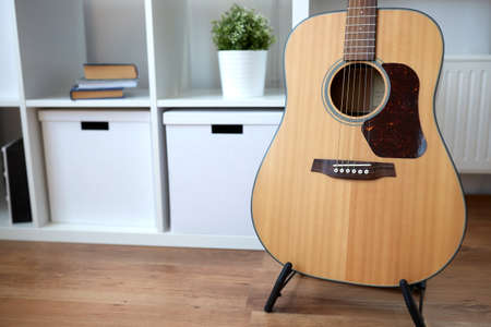 close up of acoustic guitar on stand at home