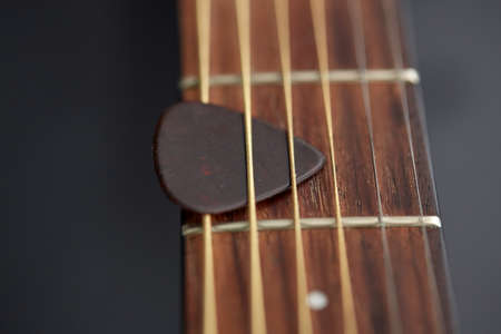 close up of guitar neck with pick between strings