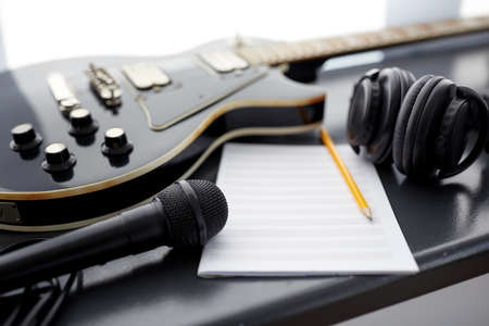 close up of guitar, music book and headphones
