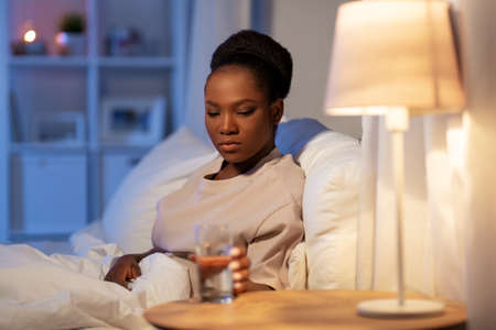 african woman drinking water in bed at night