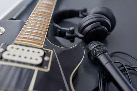 close up of bass guitar, microphone and headphones