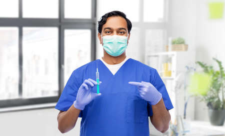 indian male doctor in mask with vaccine in syringe 스톡 콘텐츠