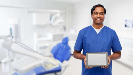 doctor or male dentist showing tablet computer