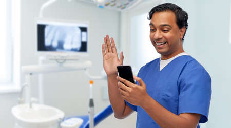 doctor or male dentist having video call on phone 스톡 콘텐츠