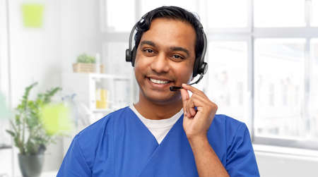 smiling indian doctor or male nurse with headset