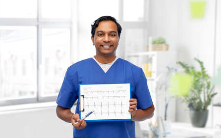 smiling male doctor with cardiogram on clipboard