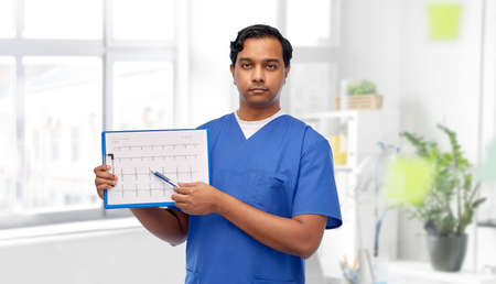 male doctor with cardiogram on clipboard