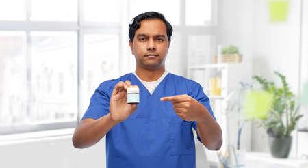indian doctor or male nurse holding medicine