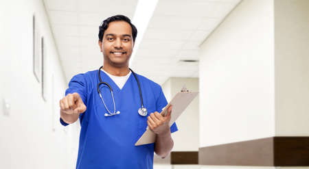 indian doctor or male nurse pointing to camera