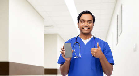 doctor or male nurse with phone showing thumbs up 스톡 콘텐츠
